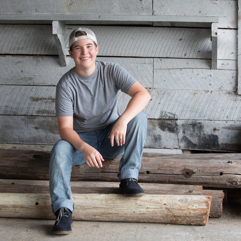 Senior Photography - Senior boy in grey sitting on log in front of wood wall