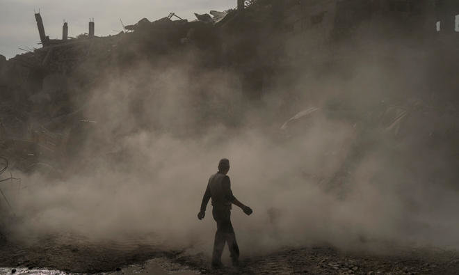 A man walks amid a cloud of duts as bulldozer remove debris from destroyed shops in the Old City of Mosul/AP