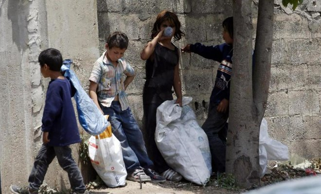 Syrian refugee children stand along a street in south of sidon , southren lebanon/REUTERS