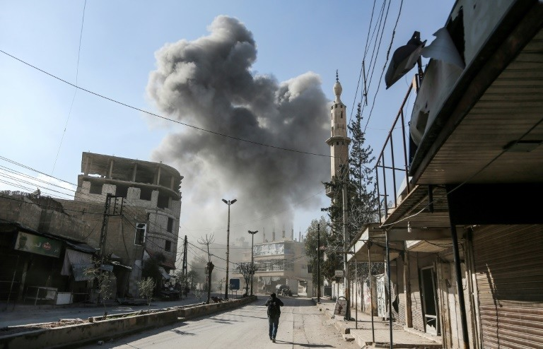 A picture taken on February 21, 2018 shows a smoke plume rising following a reported regime air strike in the rebel-held enclave of Hamouria in the Eastern Ghouta near Damascus. /AFP / ABDULMONAM EASSA