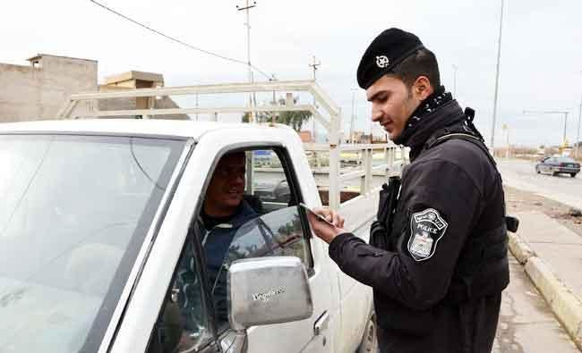 An Iraqi policeman checks the ID of a driver at a checkpoint in Mosul, in this February 22, 2018 photo, seven months after Iraqi forces retook the northern city from Daesh terrorists. (AFP)
