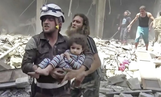 A civil defense worker carries a child after airstrikes hit Aleppo, Syria. With Russia's help, the government forces of President Bashar Assad finally seized rebel-held portions of the city of Aleppo, at a huge cost in terms of deaths and destruction. (AP)
