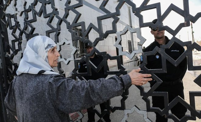 A Palestinian woman takes part in a protest calling for the Egyptian authorities to open the Rafah Border Crossing in the southern Gaza Strip on March 22, 2018. (AFP)