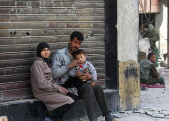 A Syrian man sits with his family at the entrance of a shrapnel riddled shop near government forces in the Eastern Ghouta town of Kafr Batna, on the northeastern outskirts of Damascus, on March 20, 2018. Government forces took control of Kafr Batna in the southern pocket of Eastern Ghouta that was held by the Faylaq Al-Rahman rebel group, on March 17. (AFP)
