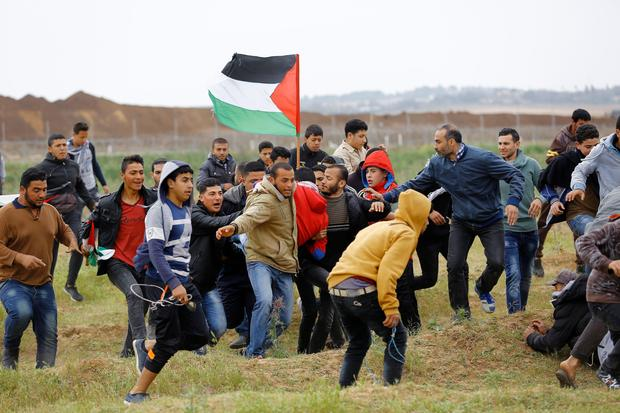 Palestinians march past a tent city erected along the border with Israel east of Gaza City in the Gaza strip to commemorate Land Day, March 30, 2018. Land Day marks the killing of six Arab Israelis during 1976 demonstrations against Israeli confiscations of Arab land.