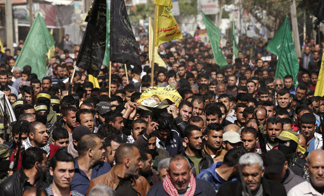 Palestinians carry the body of Hamdan Abu Amsha, who was killed a day earlier by Israeli forces when clashes erupted as tens of thousands of Gazans marched near the Israeli border with the enclave to mark Land Day, during his funeral in Beit Hanun in the northern Gaza Strip on Mar. 31, 2018. (AFP)