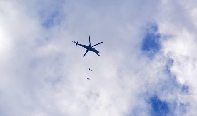 A picture taken on April 22, 2018, shows a Syrian air force Mi 24 helicopter dropping bombs over the Palestinian camp of Yarmouk, south of the Syrian capital Damascus, during regime strikes targeting Daesh in the camp. (Rami Al-Sayed/AFP