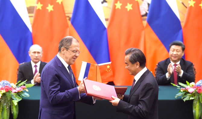 Russian Foreign Minister Sergey Lavrov and Chinese Foreign Minister Wang Yi exchange documents in Beijing's Great Hall of the People in 2016. (File/AFP)
