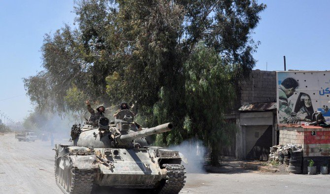 A Syrian government tank drives down a street in Al Hajar al Aswad, on April 23, 2018, during a regime offensive targeting the Islamic State group in the southern districts of Damascus. (AFP)