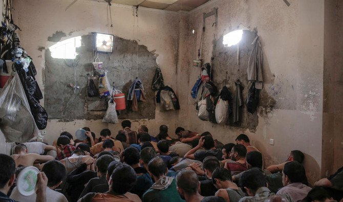 In this Tuesday, July 18, 2017 file photo, suspected Daesh members sit inside a small room in a prison south of Mosul. Iraq is holding huge numbers of detainees on suspicion of ties to the Daesh — around 11,000, according (AP Photo/Bram Janssen, File)