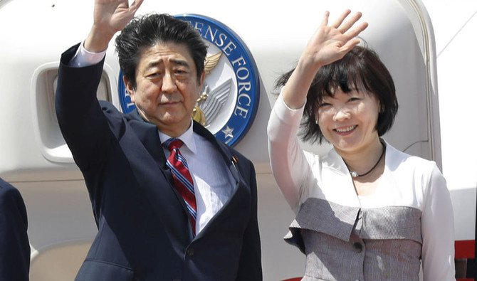 Japanese Prime Minister Shinzo Abe, left, waves with his wife Akie Abe while boarding his plane before departure for the Middle Eastern countries, at Haneda international airport in Tokyo Sunday, April 29, 2018. (Yukie Nishizawa/Kyodo News via AP)