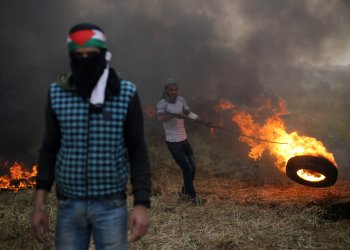 A Palestinian protester moves a burning tire during clashes with Israeli troops at Israel-Gaza border, in the southern Gaza Strip April 5, 2018. REUTERS/Ibraheem Abu Mustafa