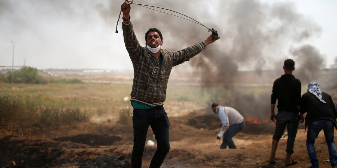 A Palestinian demonstrator shouts during clashes with Israeli troops at a protest demanding the right to return to their homeland, at the Israel-Gaza border east of Gaza City April 6, 2018. REUTERS/Mohammed Salem