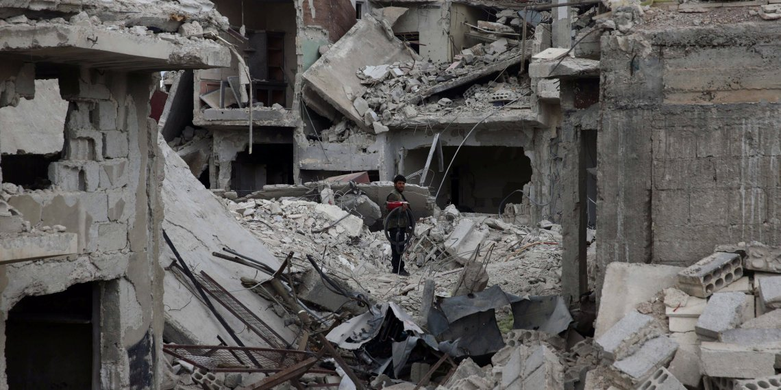 A man stands on rubble of damaged buildings in the besieged town of Douma, Eastern Ghouta, in Damascus, Syria March 30, 2018. REUTERS/Bassam Khabieh