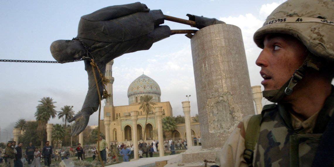 FILE PHOTO: A U.S. soldier watches as a statue of Iraq's President Saddam Hussein falls in central Baghdad, Iraq April 9, 2003. REUTERS/Goran Tomasevic/File Photo