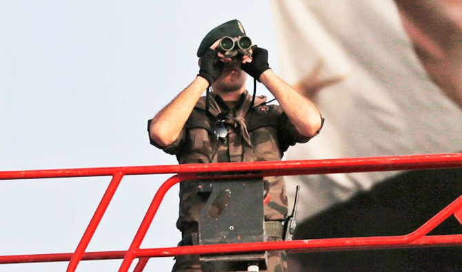 A Turkish police officer uses binoculars to scan the area from a platform, in Istanbul /AP