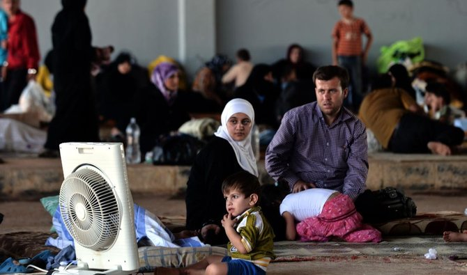 Syrian families which have been displaced due to fighting between rebel fighters and syrian government forces are seen near the syrian border with Turkey on August 25, 2012/AFP