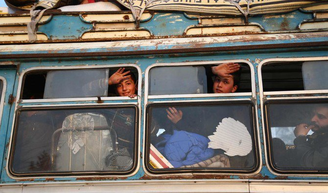 Children wave from windows as buses carrying Jaish Al-Islam fighters and their families ,from their former rebel bastion of Douma , arrive at the Abu Al-Zindeen checkpoint controlled by Turkish-backed rebel fighters near the northern Syrian town of Al-Bab -AFP