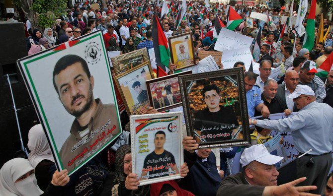 Palestinians hold portraits of relatives jailed in Israel prisons as they protest to demand for their release during a demostration to mark the Prisoners Day in the northern West Bank city of Nablus /AFP