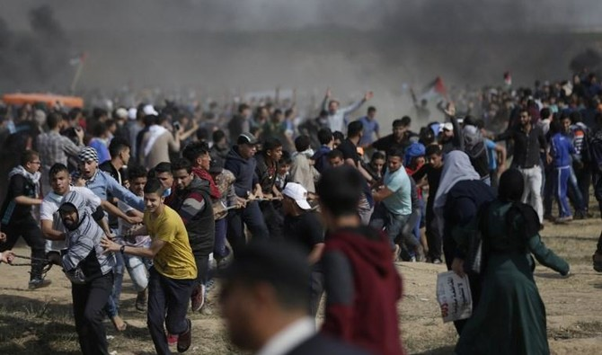 Palestinian demonstrators try to pull down part of the fence on the Israel-Gaza border, east of Gaza City in the central Gaza Strip on April 27. (AFP)