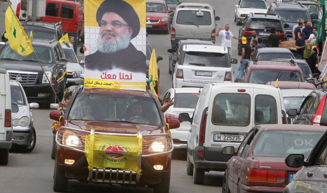 A man gestures as he drives a car with the picture of Hezbollah leader Sayyed Hassan Nasrallah on it, during the parliamentary election day, in Bint Jbeil, southern Lebanon May 6, 2018. (Reuters/Aziz Taher)