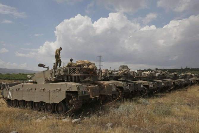 """Israeli Merkava Mark IV tanks take position near the Syrian border in the Israeli-annexed Golan Heights on May 9, 2018. The Israeli-occupied section of the Golan Heights was placed on high alert due to """"irregular activity by Iranian forces"""" across the demarcation line in Syria. (AFP)"""