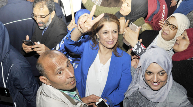 Tunisian Ennahdha party member Souad Abderrahim (C) jubilates after winning the municipal elections in front of the movement's headquarters in Tunis late on May 6, 2018. The Islamist Ennahdha movement claimed victory, after initial results gave it a lead in Tunisia's first free municipal elections since the 2011 revolution. / AFP / SOFIENNE HAMDAOUI
