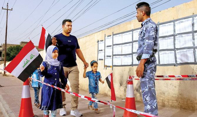 A member of the Iraqi security forces watches an man and children walk toward a polling station in the central holy city of Najaf on May 12, 2018 as the country votes in the first parliamentary election since declaring victory over the Islamic State (IS) group.  Iraq headed to the polls for its first parliamentary election since declaring victory over the Islamic State group, in hope of shoring up a fragile peace and rebuilding. / AFP / Haidar HAMDANI