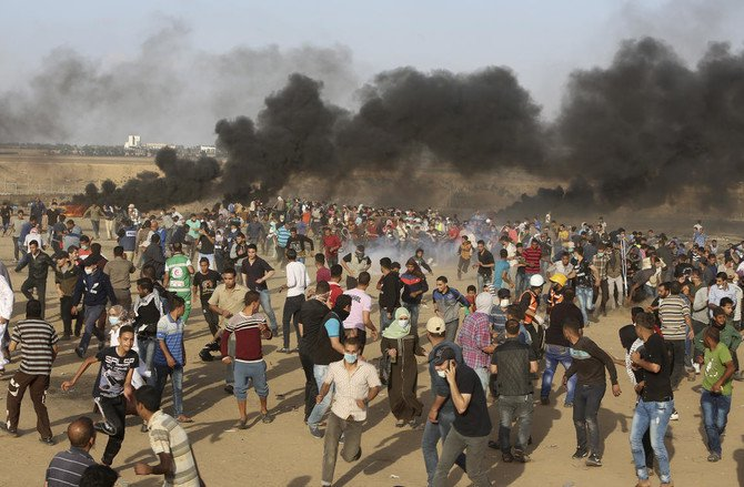 Palestinian protesters run for cover from teargas fired by Israeli troops during a protest at the Gaza Strip's border with Israel on Friday, May 11. (AP)