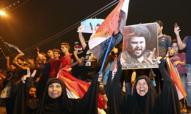 Followers of Iraqi Shiite cleric Muqtada Al-Sadr celebrate in Tahrir Square, Baghdad, on May 14, 2018. Al-Sadr is the current front-runner in national elections. (AP Photo/Hadi Mizban)