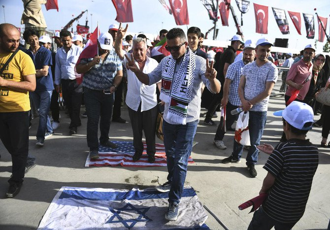 Protesters step on an Israel flag, foreground, and US flag after a rally in solidarity with Palestinians and before an extraordinary summit of the Organization of Islamic Cooperation (OIC), in Istanbul, Turkey, Friday, May 18, 2018. (AP)