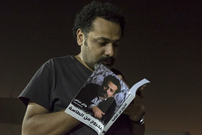 "In this June 9, 2017 photo provided by Roger Anis, prominent activist and blogger Wael Abbas signs a copy of his book, ""The theory of leaving the bowl,"" in Cairo, Egypt. Egyptian security officials said Abbas, known for documenting police abuse, was detained, Wednesday, May 22, 2018, the latest in a new wave of arrests since elections earlier this year. The officials said Abbas was held on accusations of disseminating false news and joining an outlawed group, among other charges. (Roger Anis via AP)"