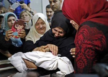 The mother of a Leila Al-Ghandour (C), a Palestinian baby of 8 months who according to Gaza's health ministry died of tear gas inhalation during clashes in East Gaza the previous day, holds her at the morgue of Al-Shifa hospital in Gaza City. (AFP)