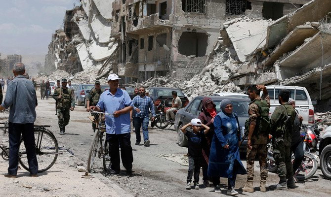 Pro-government forces stand in the destroyed Thalateen Street in the Yarmuk Palestinian refugee camp on the southern outskirts of the capital Damascus on May 24, 2018, as civilians return to see their homes after the regime seized the camp and adjacent neighborhoods of Tadamun and Hajar al-Aswad earlier in the week from the Daesh group. (AFP / LOUAI BESHARA)
