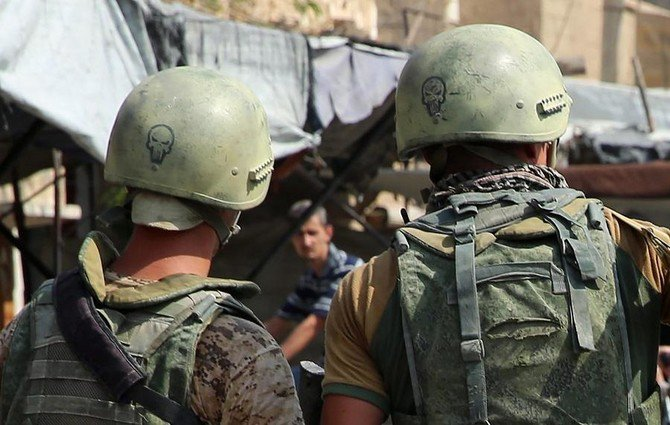 Russian soldiers standing guard in a central street in Syria's eastern city of Deir Ezzor, as locals pass by. /(AFP)