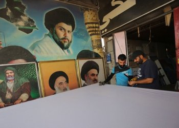 Iraqis work on a poster of Shiite cleric Moqtada Sadr at a printing shop in Sadr City, east of the Baghdad on May 23, 2018.(AFP / AHMAD AL-RUBAYE)