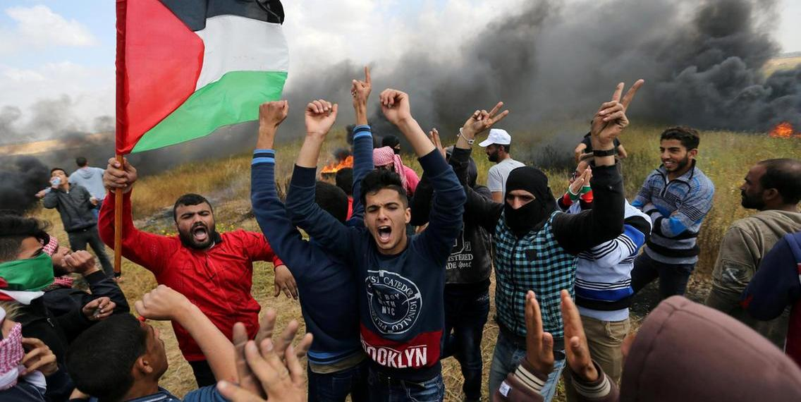 Palestinians flee as Israeli tear gas grenades begin to drop on a demonstration near the Gaza Strip's border with Israel on March 30, 2018, the first day of a six-week tent protest called for by Hamas. Mahmud Hams / AFP