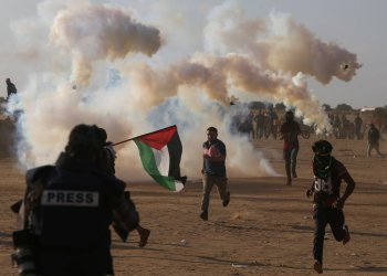 Palestinian demonstrators run from tear gas fired by Israeli troops during a protest marking the 70th anniversary of Nakba, at the Israel-Gaza border in the southern Gaza Strip May 15, 2018. REUTERS/Ibraheem Abu Mustafa