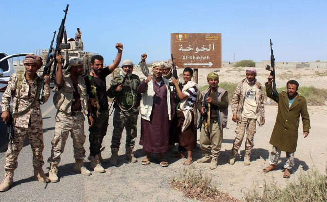 Yemeni fighters loyal to the Saudi-backed Yemeni president gesturing and shout slogans as they stand on a road leading to the town of Khokha. (AFP)