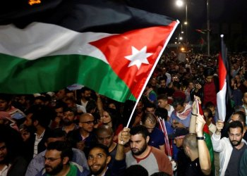 A protester holds up a Jordanian national flag during a protest in Amman on June 4, 2018. (REUTERS/Muhammad Hamed)