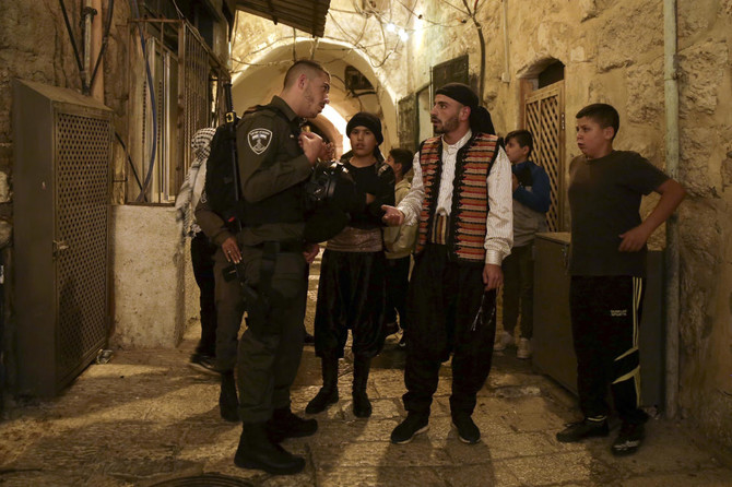 n this Tuesday, June 5, 2018 photo, traditionally dressed Palestinian public wakers, known as musaharati, are stopped by the Israeli border police in the Jerusalem's Old City. (AP)