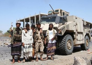 File photo showing fighters loyal to the Saudi-backed Yemeni government pose in front of an armored vehicle in the western Yemeni coastal town of Mokha. (AFP)