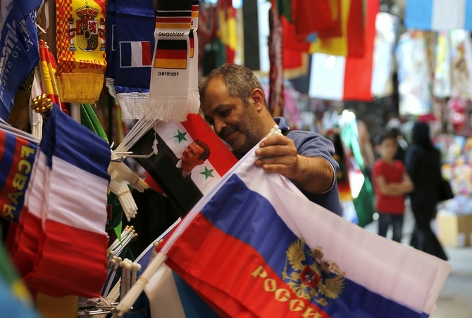 A picture taken on June 7, 2018 shows flags of countries participating in the upcoming 2018 FIFA World Cup on display among other flags outside a vendor's stall to be sold for football supporters and viewers, at a market street in the old city of the Syrian capital Damascus. / AFP PHOTO / LOUAI BESHARA