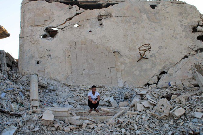 Moawiya Sayasina, the Syrian activist who started scribbling anti-Assad slogans in 2011, sits among the rubble in a rebel-held neighbourhood in the southern Syrian city of Daraa on June 5, 2018. (Mohamad Abazeed/AFP)