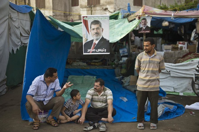 Egyptian protesters rest under a portrait of Egypt's deposed president Mohamed Morsi during a sit-in in his support outside Rabaa Al-Adawiya mosque in Cairo on August 4, 2013. (AFP)