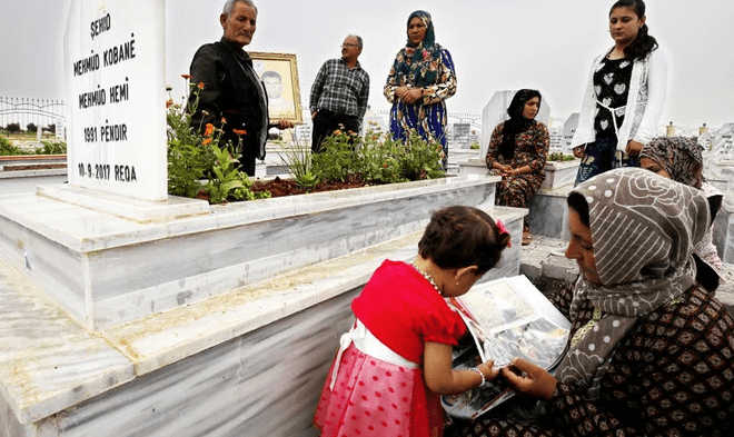 Hundreds of identical tombs are arranged in rows, topped with planters holding yellow daisies and red roses that rise up to meet silvery headstones. (AFP)