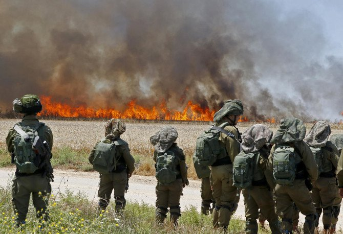 Israeli soldiers face the smoke from a fire caused by incendiaries tied to kites flown by Palestinian protesters. (File/AFP)