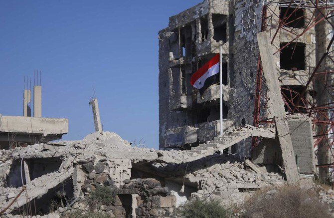 The Syrian national flag rises in the midst of damaged buildings in Daraa-Al-Balad, an opposition-held part of the southern city of Daraa, on July 12, 2018. (AFP)