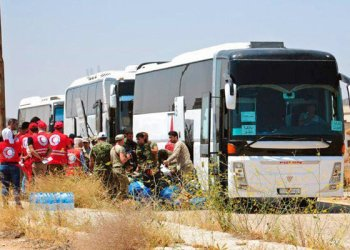 Syrian government forces and Syrian Arab Red Crescent oversee the evacuation by buses of opposition fighters and their families from the southern province of Daraa, Syria, in this July 15, 2018 photo. (AP)
