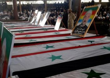 A picture from the official Syrian Arab News Agency (SANA) shows coffins lined up during a mass funeral on July 26, 2018 following deadly suicide attacks in the southern city of Sweida